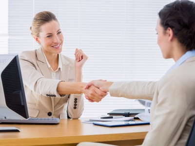 Smartly dressed yyoung women shaking hands in a business meeting at office desk